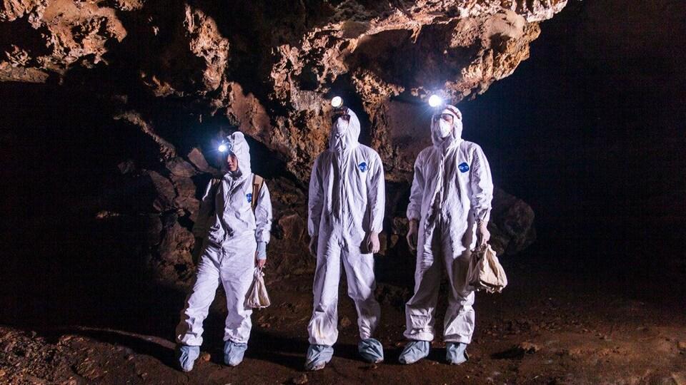 On voit trois personnes en combinaison blanche et munies de lampes-torches qui explorent une grotte. Elles tiennent un sac dans la main.