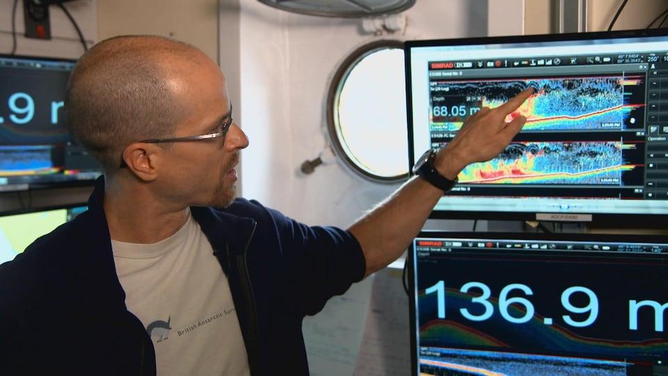 On voit M. Chavanne qui montre sur un écran d'ordinateur une représentation des vagues sous-marines dans le fjord du Saguenay.