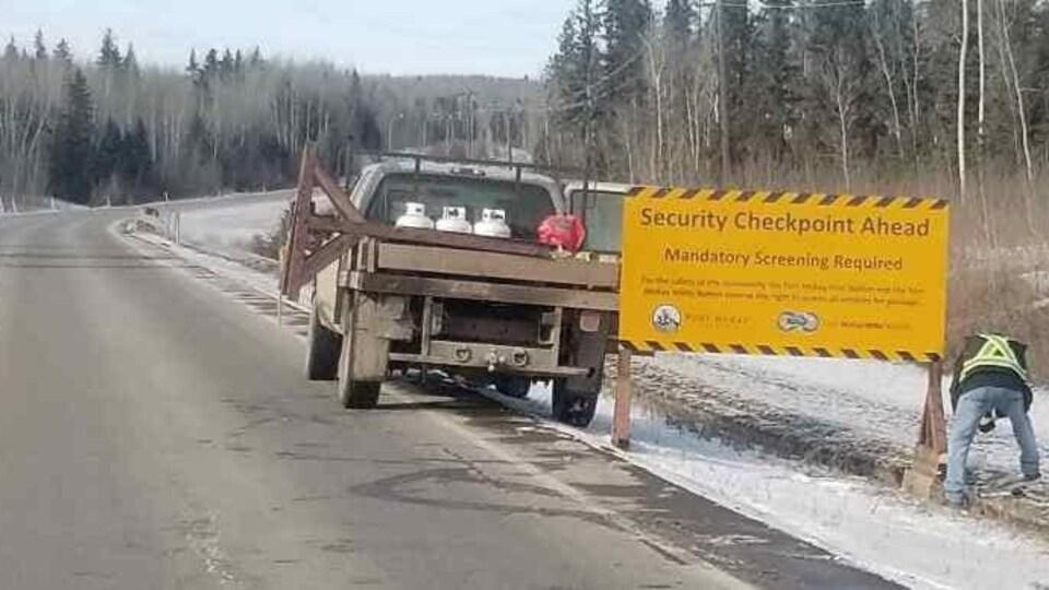 Un homme installe une pancarte sur le bord d'une route. On peut y lire en anglais contrôle de sécurité, dépistage obligatoire.