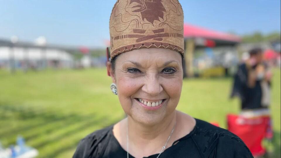 Une femme souriante qui porte une coiffe autochtone.