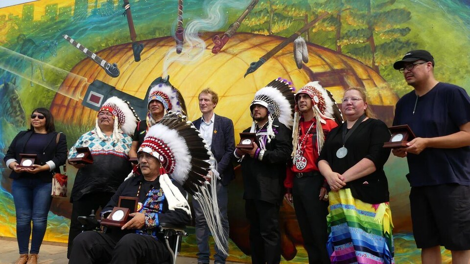 Huit chefs, dont certains portent des coiffes traditionnelles, debout autour de Marc Miller, qui porte une veste.