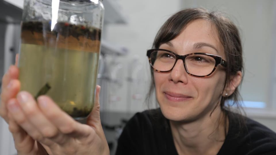 La scientifique tient dans ses mains un bocal contenant de l'eau et des particules de microplastiques.