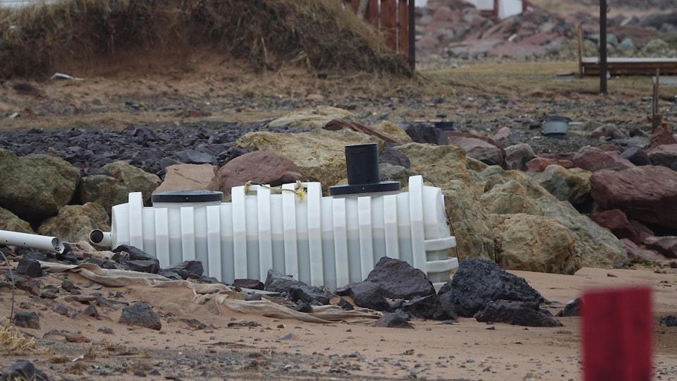 Une fosse septique qui sort du sable.