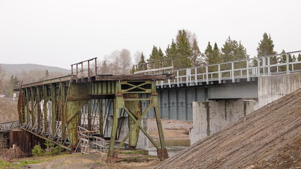 Un nouveau pont d'acier derrière un ancien pont ferroviaire rouillé.