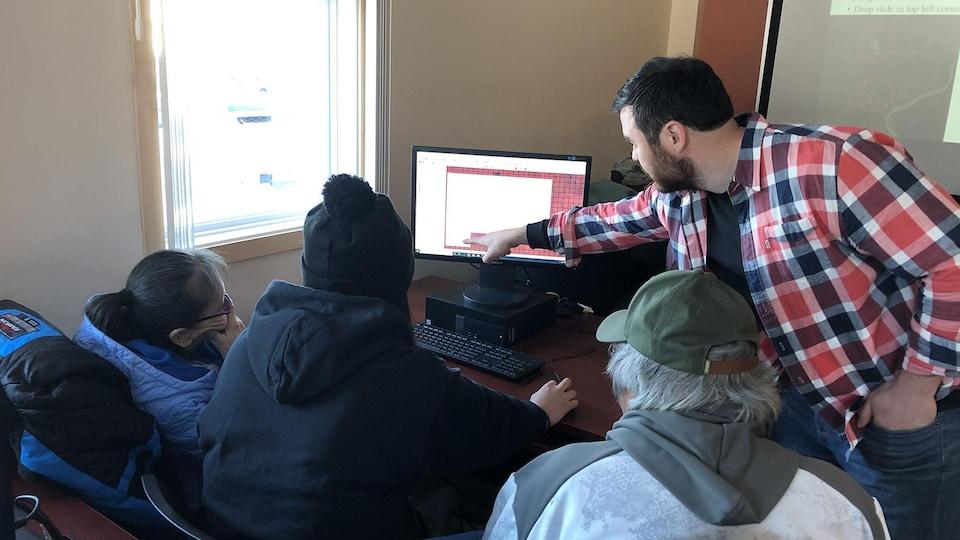 Quatre personnes travaillent inscrivent des données à l'ordinateur.