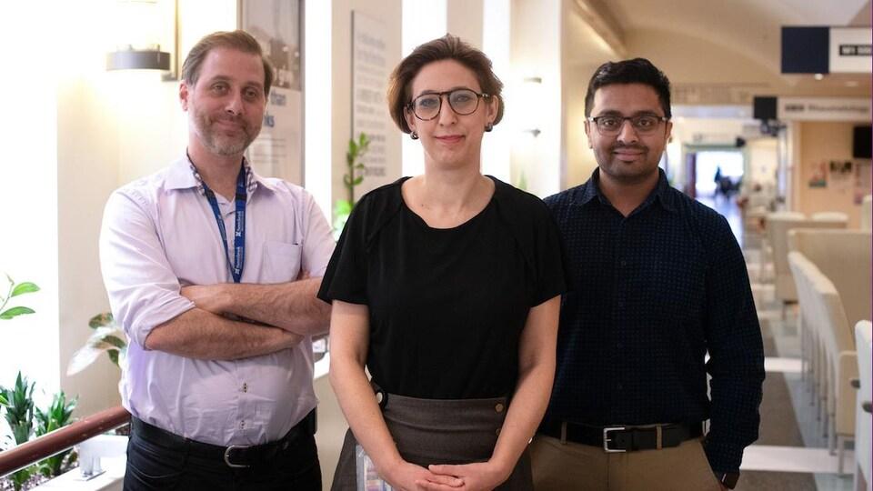 Trois chercheurs sont regroupés dans le corridor d'un hôpital et sourient.