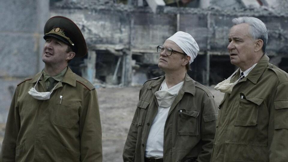 Trois hommes se tenant devant un bâtiment en décrépitude observent quelque chose.
