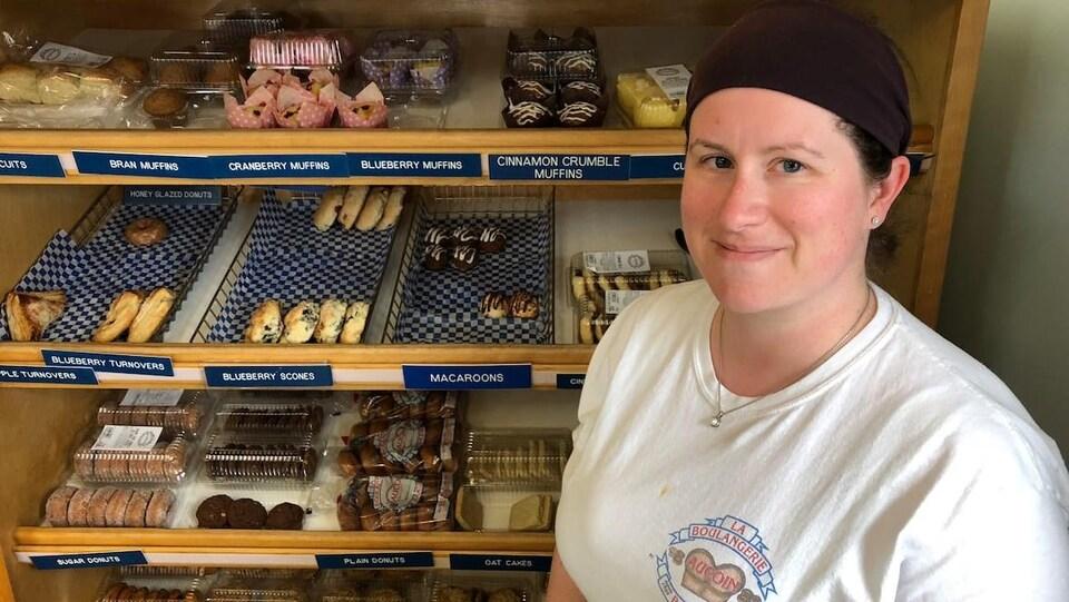 Jenny Aucoin devant un étalages de beignets et d'autres pâtisseries
