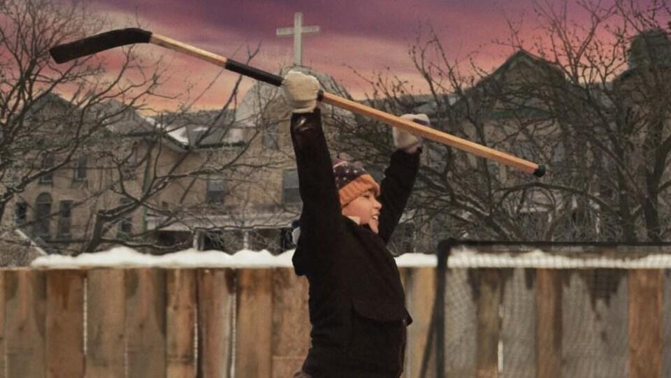 Un garcon tient son bâton de hockey au bout de ses bras dans les airs.