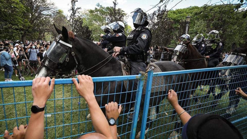 Des policiers à cheval face à des manifestants.