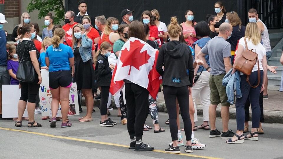 Plusieurs personnes sont rassemblées dehors et arborent le drapeau canadien.
