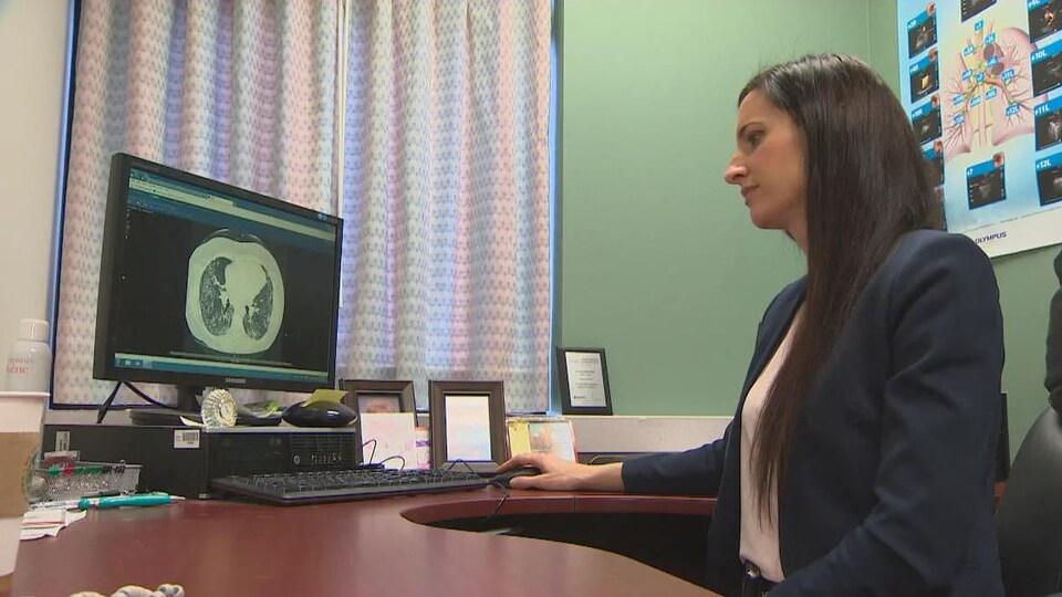La médecin assise à son bureau étudie une radiographie.