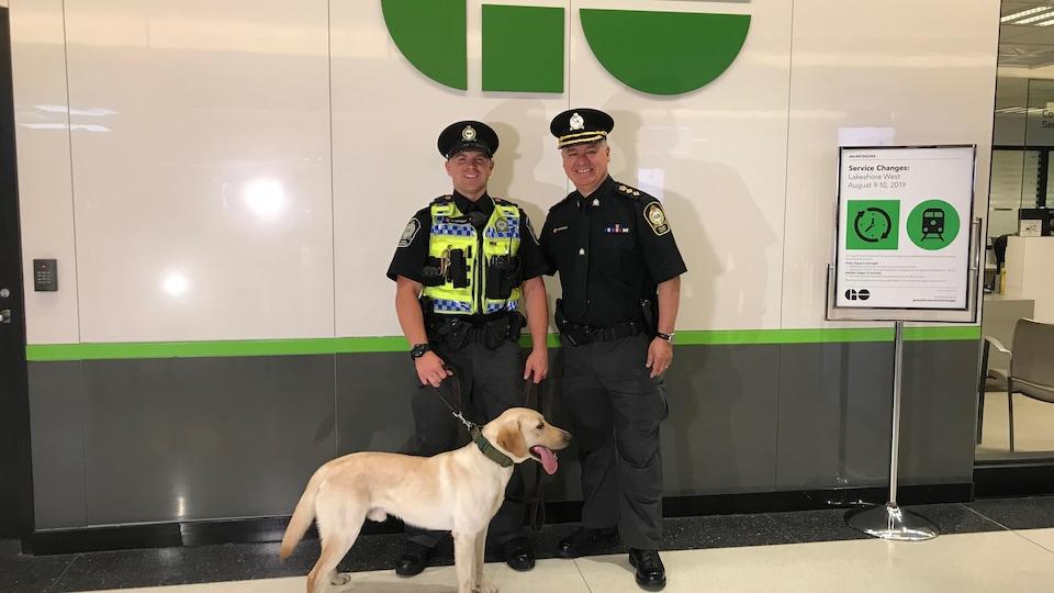 Photo de deux hommes debout portant des uniformes d'agents de sécurité; l'un d'eux tient un chien en laisse.