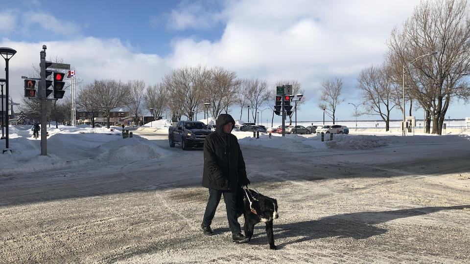 Jimmy Turgeon-Carrier marche dans la rue avec son chien-guide.