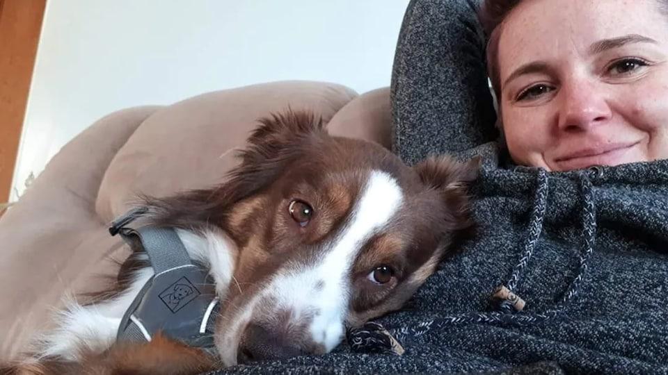 Autoportrait de Megan Bolen et son chien assis sur un divan.