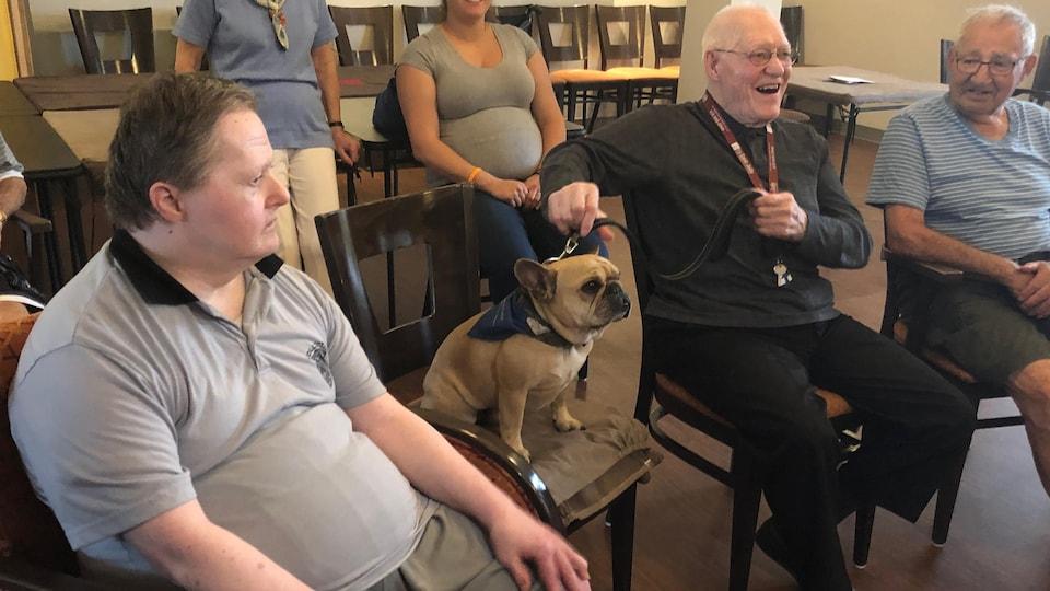 Un chien assis près d'un homme âgé.