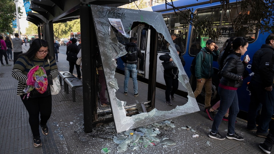 Des gens contournent la vitre brisée d'un abribus pour monter dans un autobus.