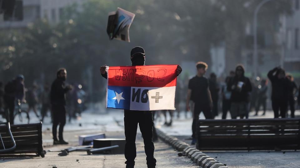 Un manifestant tient en main le drapeau du Chili.