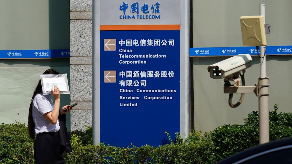 Une femme cache son visage en passant devant les bureaux de China Telecom, à Pékin.