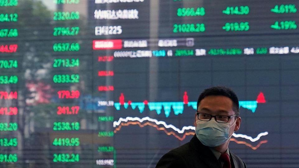 Un homme avec un masque protecteur à la Bourse de Shanghai, dans le district financier de Pudong. En toile de fond, un immense tableau numérique présentant l'évolution des cours boursiers.