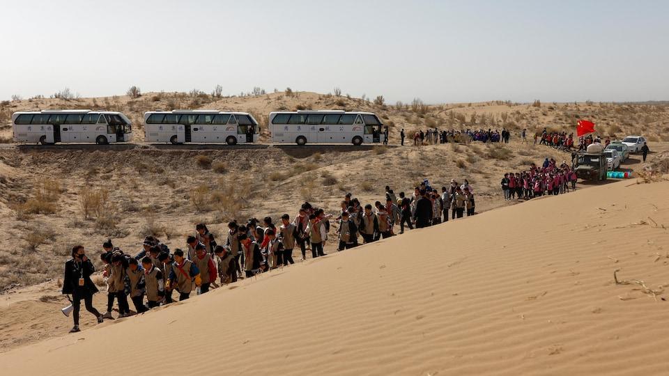 Des classes enfants descendent une dune de sable.
