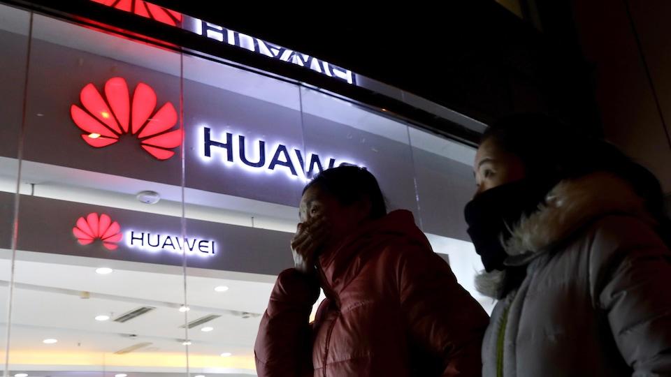 Deux femmes passent devant un magasin du géant chinois Huawei.
