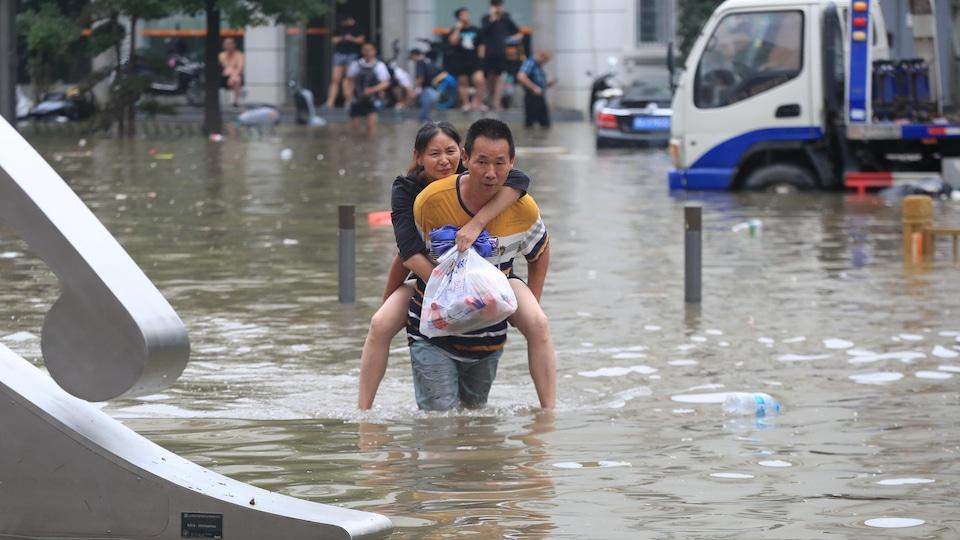Un homme portant une femme traverse une route inondée à la suite de fortes pluies à Zhengzhou en Chine.