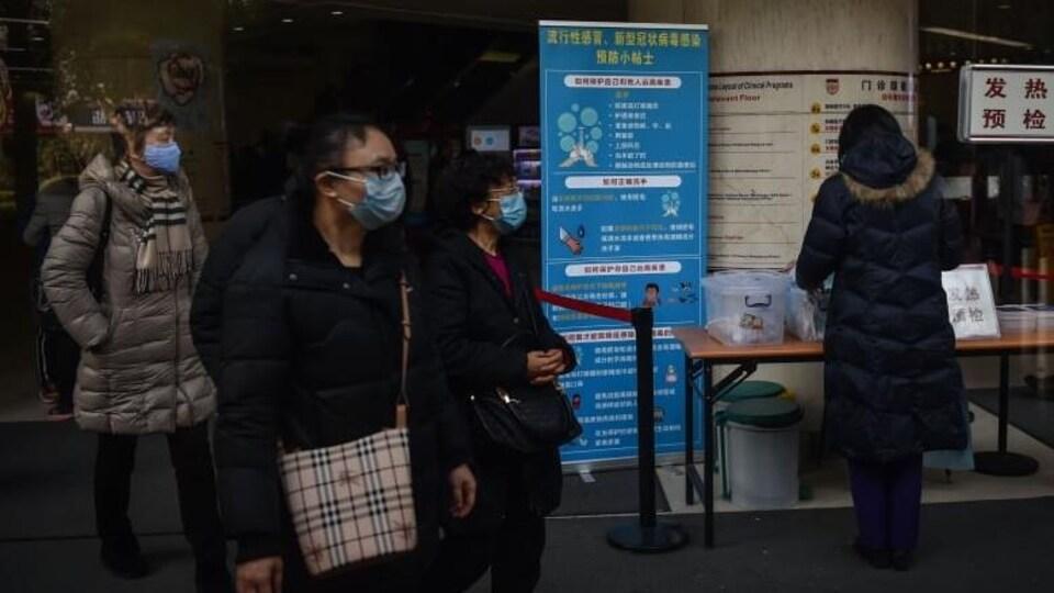 Des chinois portants des masques de protection bleus pour ne pas attraper le virus.