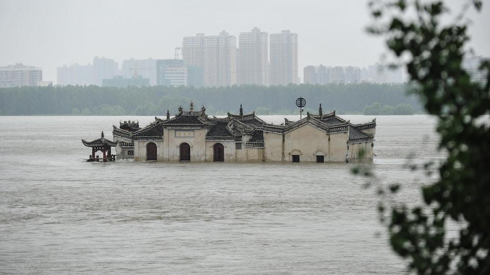 Un temple à moitié submergé est le seul bâtiment au milieu d'une étendue d'eau. Au loin se trouvent des immeubles d'habitation.