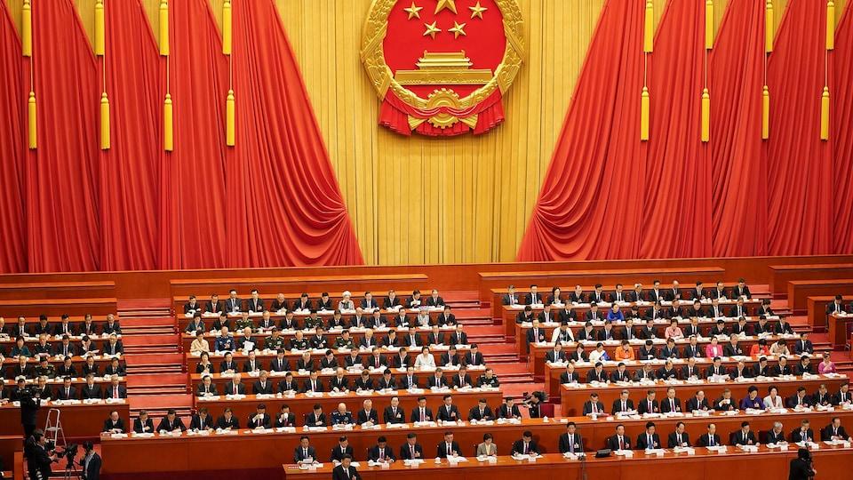 Des dizaines de dignitaires sont assis devant un énorme sceau aux couleurs du drapeau chinois.