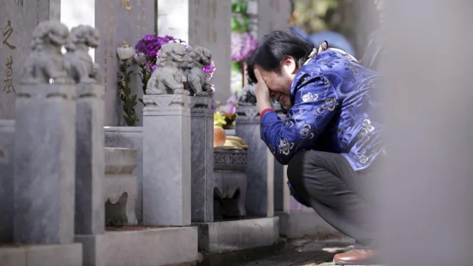 Une femme pleure devant une tombe.
