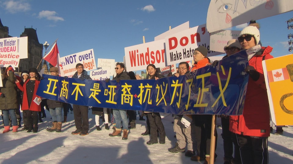 Des membres de la communauté chinoise tiennent une banderole bleue et jaune sur laquelle il est écrit en chinois.
