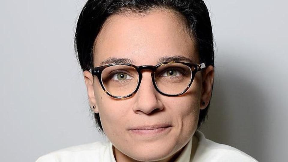 Portrait de Chloé Robichaud qui porte des lunettes et un chandail blanc
