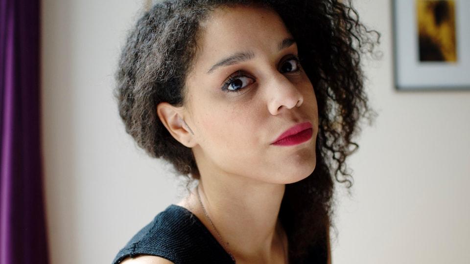 Portrait de l'auteure Chloé Savoie-Bernard, de trois-quart, la tête légèrement penchée en arrière, avec du rouge à lèvres.