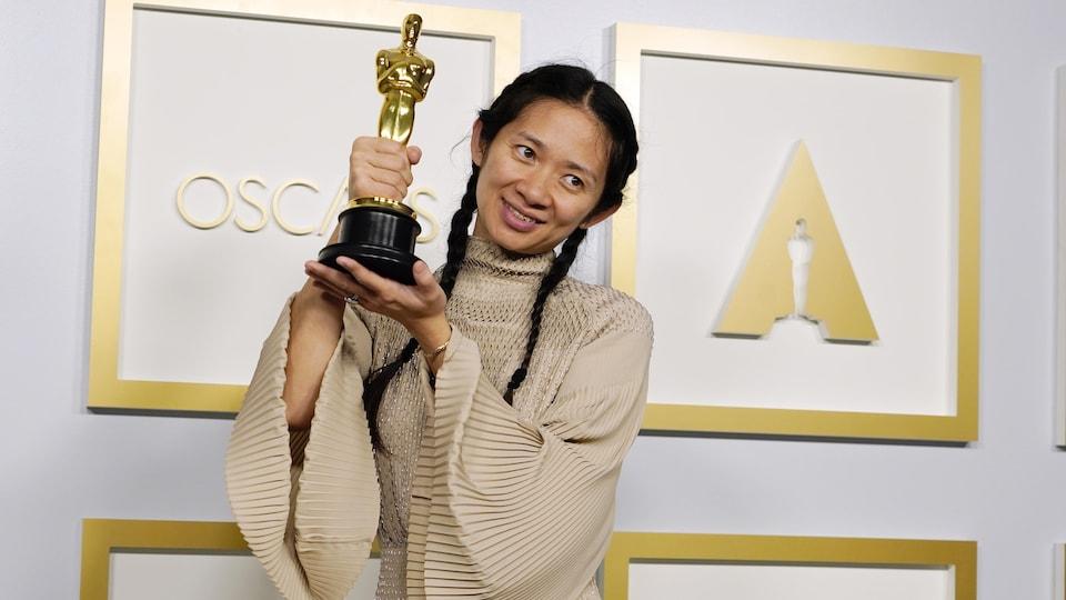 Chloé Zhao tient sa statuette haut dans les mains, près de son visage.