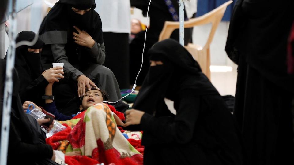 Un enfant intubé est entouré de femmes vêtues de niqabs.