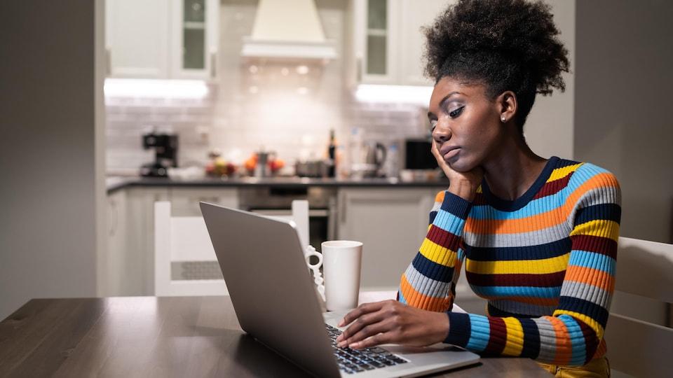 Une femme noire à la recherche d'un emploi devant son ordinateur.