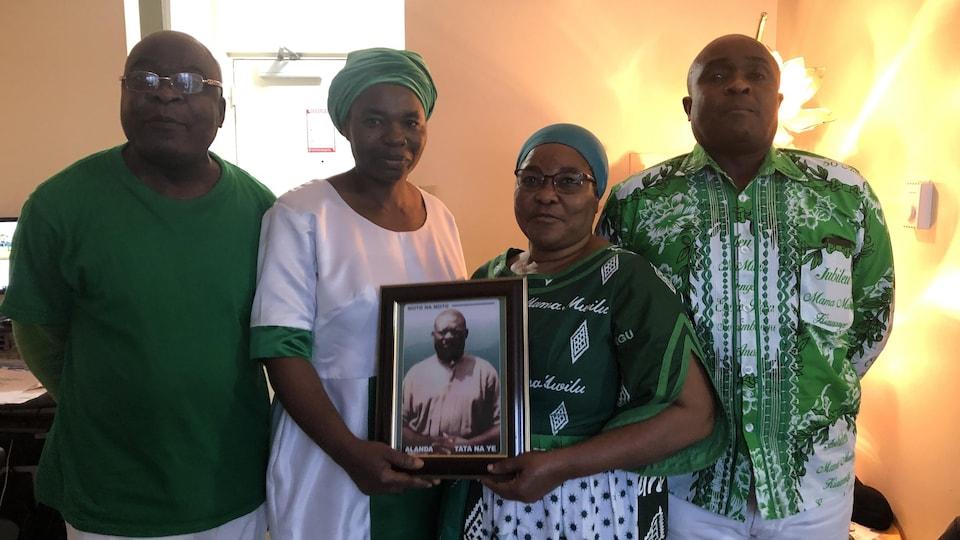Quatre personnes habillées en vert. Deux d'entre elles tiennent un portrait.