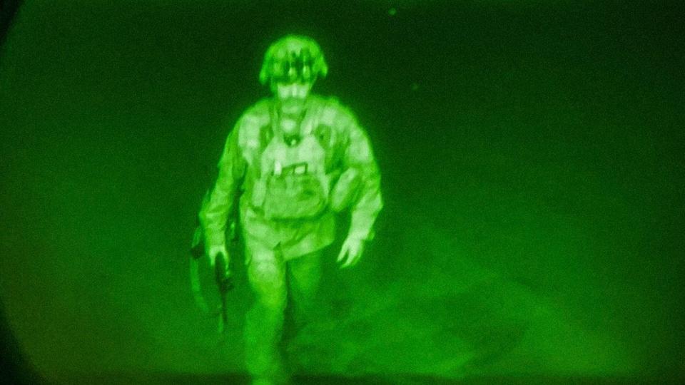 Un militaire en habit de combat monte dans un avion.