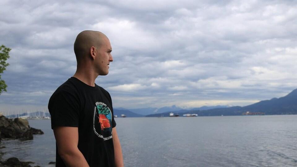 Chris Samson, sur une plage de Vancouver, regarde au loin.