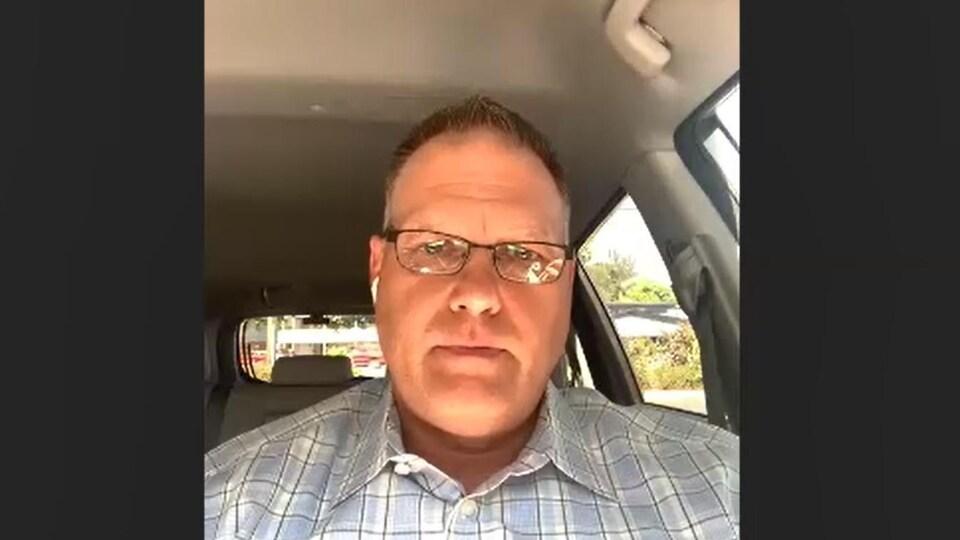 Un homme assis dans une voiture, lors d'un appel en vidéoconférence.
