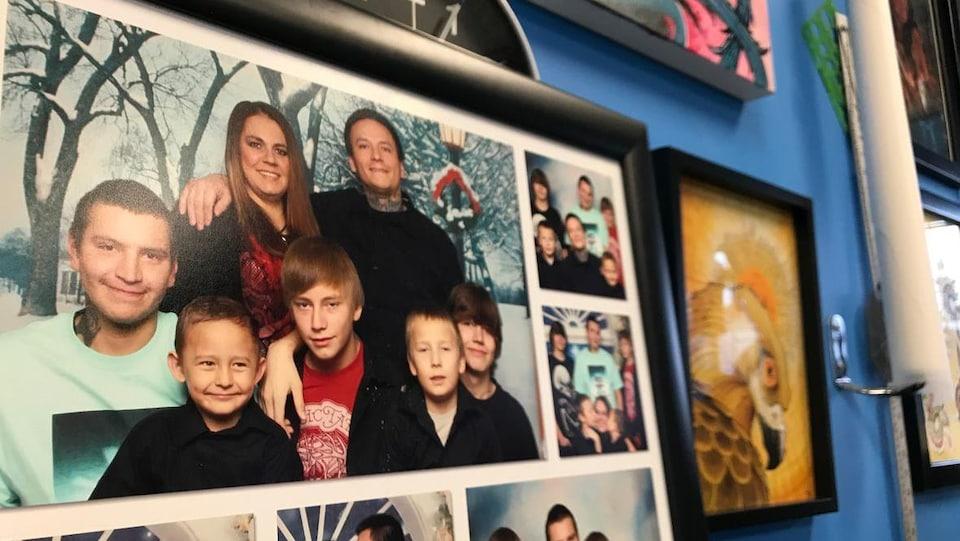 Un cadre comportant plusieurs photos de famille est sur contre un mur où se trouvent d'autres photos encadrées. On y voit un couple souriant posant avec cinq garçons.