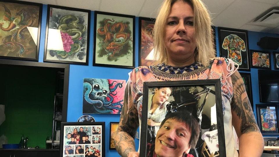 Dan un salon de tatouage une femme tient une photo encadrée d'elle et de son mari plus jeunes, faisant des grimaces à l'objectif. Sur le mur derrière elle, de nombreux dessins de tatouages sont exposés dans des cadres.