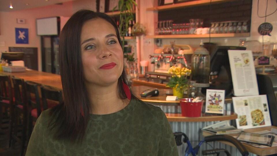 Christa Guenther devant un bar dans un restaurant.