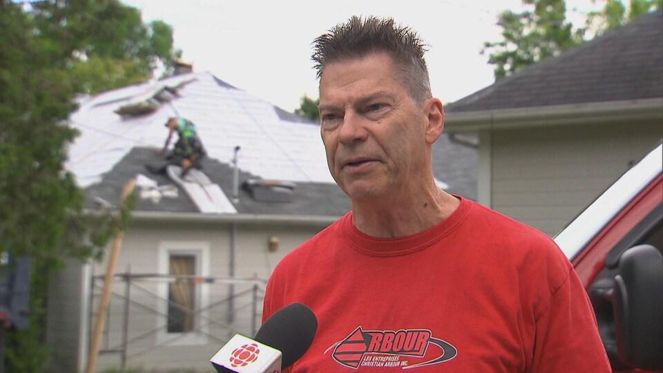 Un ouvrier s'affaire sur un toit en arrière-plan