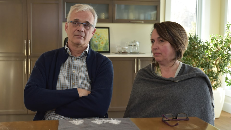 Les deux parents assis à table