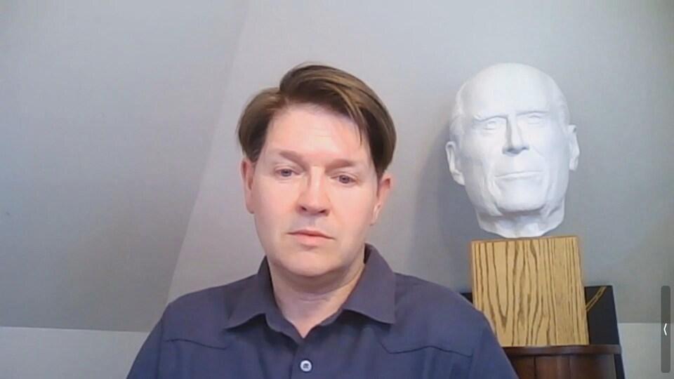 L'artiste Christian Corbet devant une sculpture.