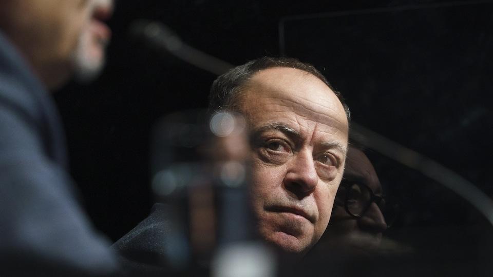 Gros plan de Christian Dubé et le reflet d'Horacio Arruda durant une conférence de presse.
