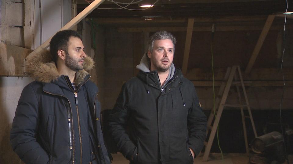 Deux hommes en manteau dans un sous-sol en construction.