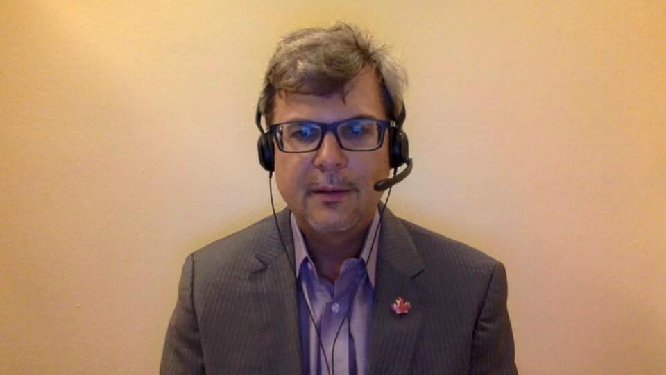 Un homme, portant une chemise et un casque d'écoute, assis devant un fond jaune, en vidéoconférence.
